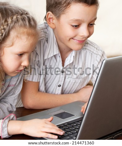 Children with laptop indoors. Happy kids playing computer at home. - stock photo