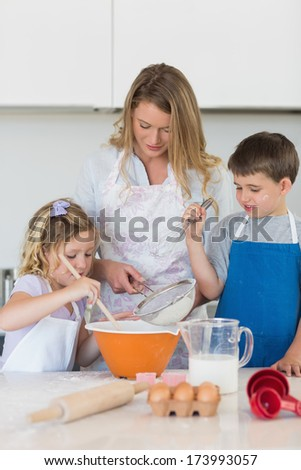 Children with mother baking cookies at counter top in kitchen