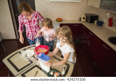Children with mother preparing breakfast at home.