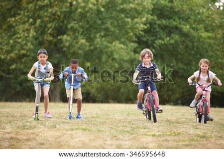 Children with mountainbike and scooter racing at the park