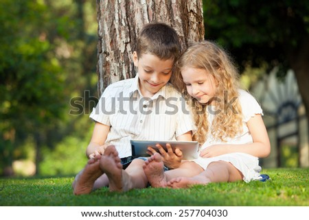 Children with tablet pc outdoors. Girl and boy on grass with computer - stock photo