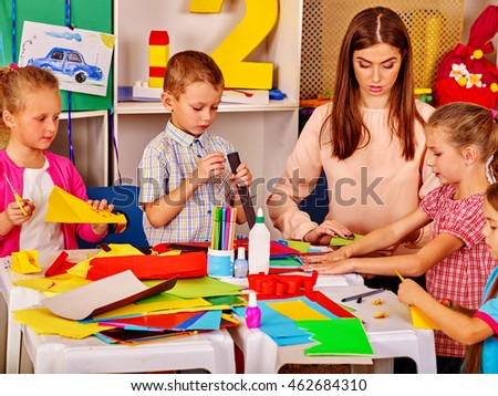 Children with teacher making something out of colored paper in primary school. Children paper craft lesson in primary school.