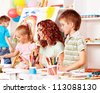 Children with teacher painting at easel in school. - stock photo