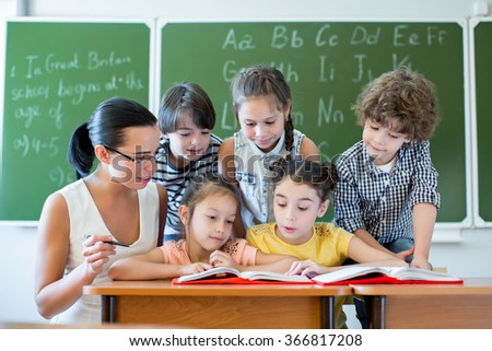 Children with teacher reading a book - stock photo