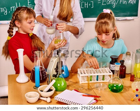 Children with teacher sitting by desk in chemistry class. - stock photo