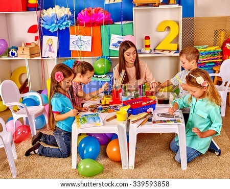 Children with teacher woman learning painting on paper at table  in  kindergarten .  - stock photo