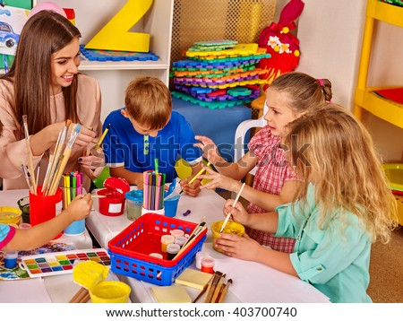 Children with teacher woman painting on paper at table  in  kindergarten .  Children paint the kids' club. - stock photo