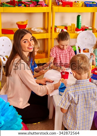 Children with teacher woman painting on paper at table  in  kindergarten . Looking in camera. - stock photo