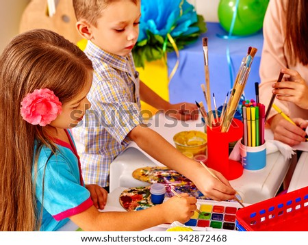 Children with teacher woman painting on paper at table  in  kindergarten . Two kids and one adult. - stock photo