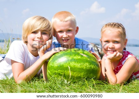 Children with  watermelon lying in green drass on blue sky background