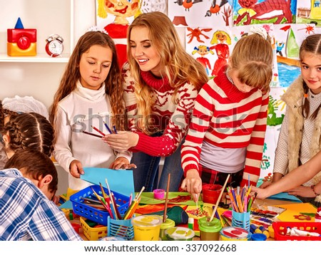 Children with young teacher  painting at art school. Education. - stock photo