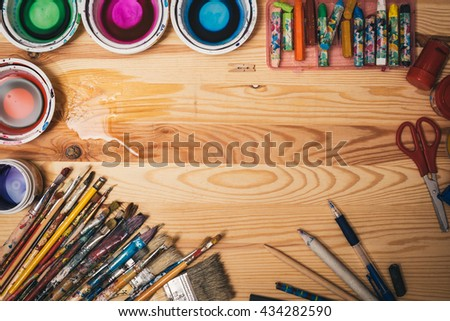children workshop instruments on wooden board for painting with copy space. Used colorful paintbrushes and crayons. - stock photo