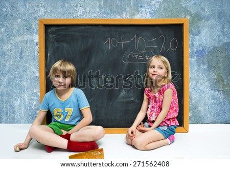 Children write on the blackboard