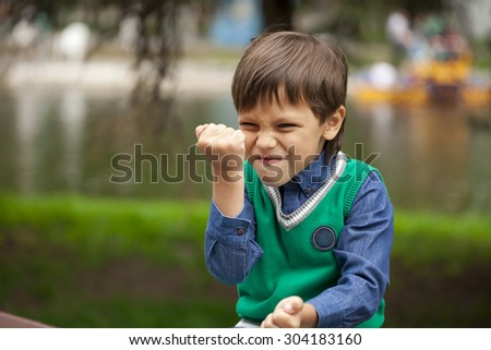 Childrens aggression, Portrait of little boy outdoor at the summer day - stock photo