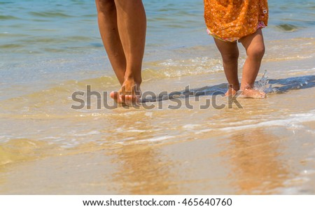 childrens and adults feet on the beach, a mother with a child, happy family