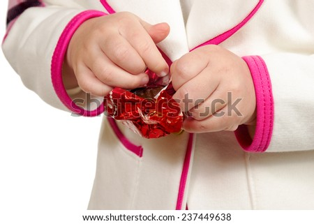 Childrens hands deploy the red wrapper with chocolate candies closeup isolated on white background - stock photo
