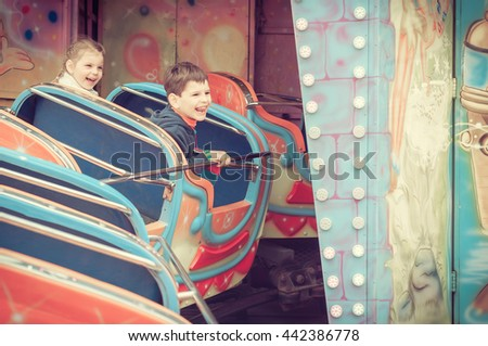 Childrens in amusement park. Kids having fun. Funny kids and happy childhood. - stock photo