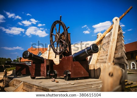 Childrens playground in a reconstruction of an old pirate ship with cannons and helm. - stock photo