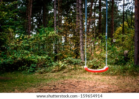 Childrens playground swing in the middle of the forest - stock photo