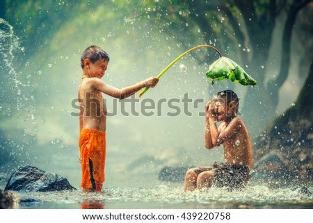 Childrens playing and splashing in the river - stock photo