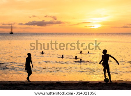 Childrens silhouette playing soccer at Tarrafal beach in Santiago island in Cape Verde - Cabo Verde - stock photo