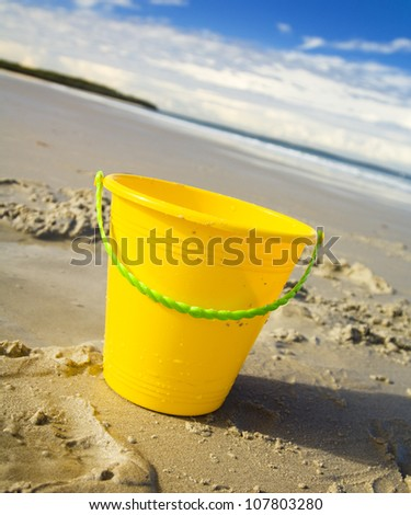 Childrens toy bucket in the sand at the beach - stock photo
