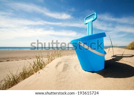 Childs bucket and spade or sand pail and shovel at the beach on a sunny summer day - stock photo
