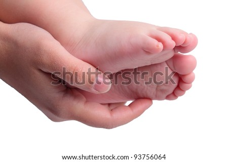 Childs feets in mother hand on white
