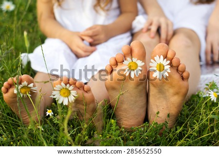 Childs feets with daisy flower on green grass in a green field - stock photo