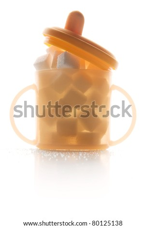 childs fruit juice, water or milk beaker filled with sugar cubes isolated on white background - stock photo