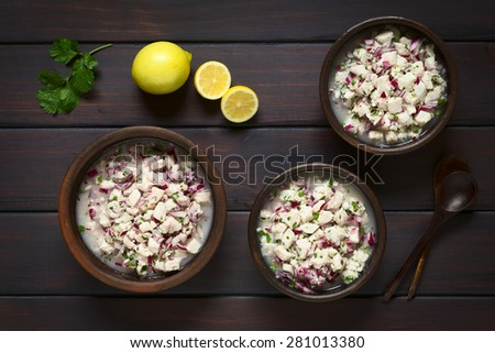 Chilean Ceviche made of Southern Ray's bream fish (lat. Brama Australis, Spanish Reineta), onion, garlic, cilantro in lemon juice in rustic bowls, photographed overhead on dark wood with natural light - stock photo