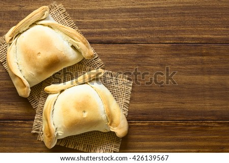 Chilean Empanada, a baked pastry stuffed with meat, photographed overhead on dark wood with natural light