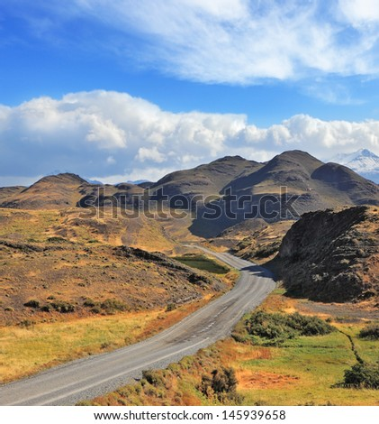 Chilean Patagonia. Summer in the national park Torres del Paine. A gravel road winds among the hills and mountains