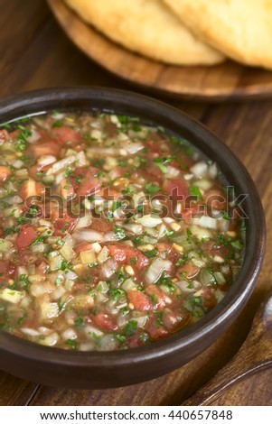 Chilean Pebre sauce, a traditional condiment made of tomato, onion, garlic, spicy aji pepper, coriander, photographed on dark wood with natural light (Selective Focus, Focus one third into the image) - stock photo
