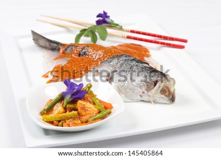 Chilean seabass with spicy sauce and a vegetable pickle side dish. - stock photo