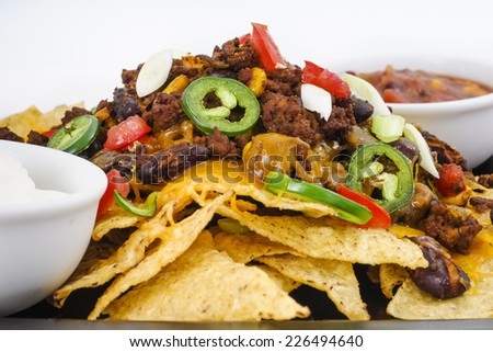 Chili and Cheddar Cheese Nacho platter with fresh Tomatoes, Onions, Jalapeno Peppers, Sour Cream and Salsa - stock photo