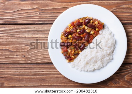 Chili con carne and rice on a white plate on a wooden background. horizontal top view  - stock photo