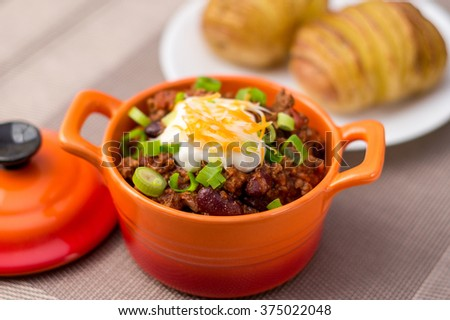 Chili Con Carne. Fresh homemade bowl of chili con carne, with beans, sour cream, grated cheddar cheese and green onions, served with hasselback potatoes on the side. - stock photo