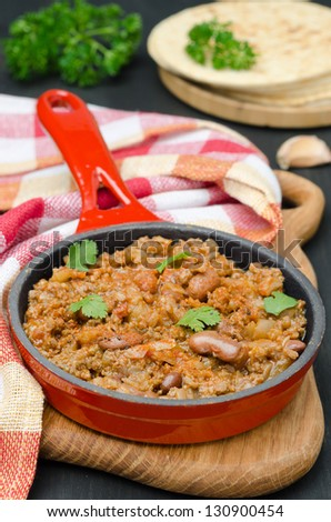 chili con carne in a cast iron skillet on a wooden board - stock photo