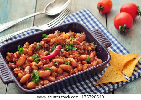 Chili Con Carne in baking mold with tortilla chips on wooden background - stock photo