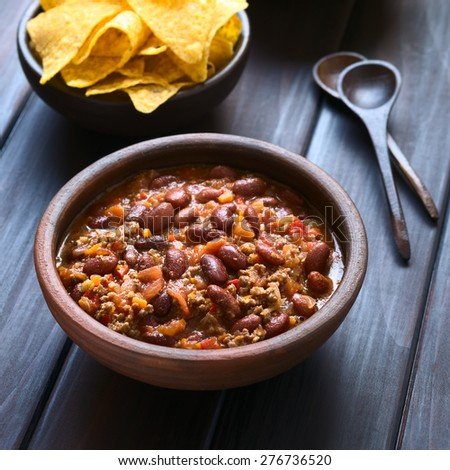 Chili con carne in rustic bowl with tortilla chips in the back, photographed on dark wood with natural light (Selective Focus, Focus in the middle of the chili) - stock photo