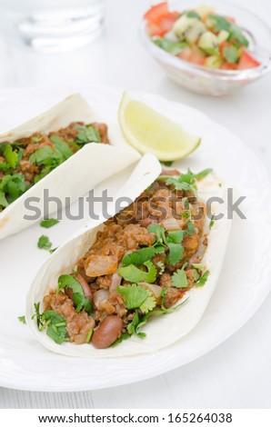 chili con carne in wheat tortillas on a plate closeup vertical - stock photo