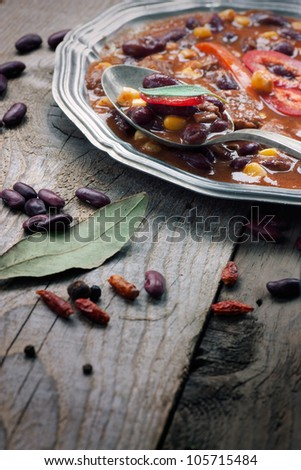 Chili con carne. Restaurant food concept with Mexican traditional dish stew in rustic setting - stock photo