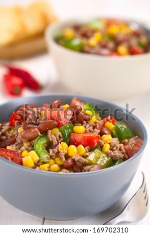 Chili con carne salad made of mincemeat, kidney beans, green bell pepper, tomato, sweet corn and red onions served in bowls with fork on the side (Selective Focus, Focus in the middle of the salad) - stock photo