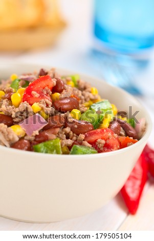 Chili con carne salad made of mincemeat, kidney beans, green bell pepper, tomato, sweet corn and red onions served in bowl with chili on the side (Selective Focus, Focus in the middle of the salad) - stock photo