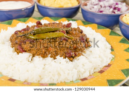 Chili con Carne - Spicy minced beef stew with chilies served over boiled rice. Sides or diced onions, grated cheese, sour cream and corn chips. - stock photo