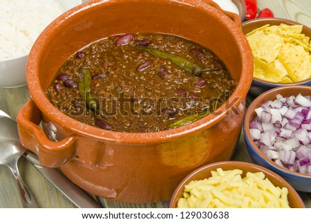 Chili con Carne - Spicy minced beef stew with chilies. Sides of diced onions, grated cheese,  white rice, sour cream and corn chips. - stock photo
