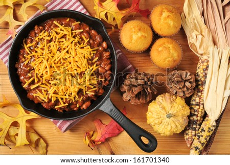 Chili con carne with cheese and corn bread muffins shot from above - stock photo
