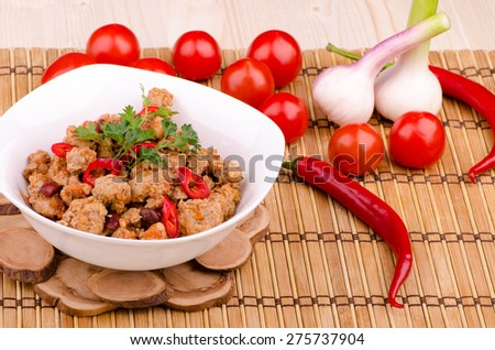 chili con carne with vegetables and beans in a white plate on a wooden stand, macro - stock photo