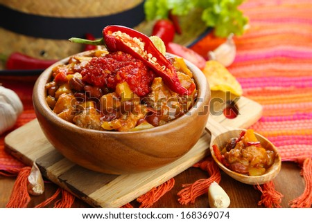 Chili Corn Carne - traditional mexican food, in wooden bowl, on napkin, on wooden background - stock photo
